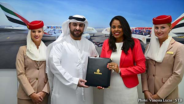 Agreement: Orhan Abbas of Emirates Airlines, centre, with Sherin Francis of the STB